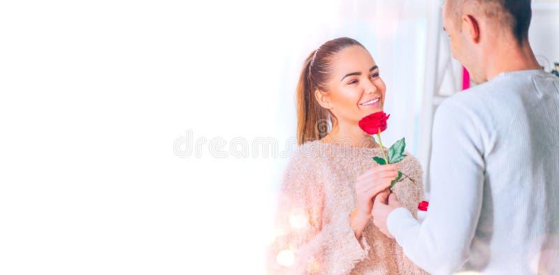 St华伦泰` s日 概念亲吻妇女的爱人 给花的年轻人他的女朋友 库存图片