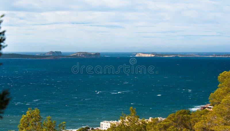 从St安东尼de Portmany,伊维萨岛的小山侧视图,到拜雷阿尔斯海里在一个晴天在11月,著名遥远的Conejera海岛 免版税库存照片