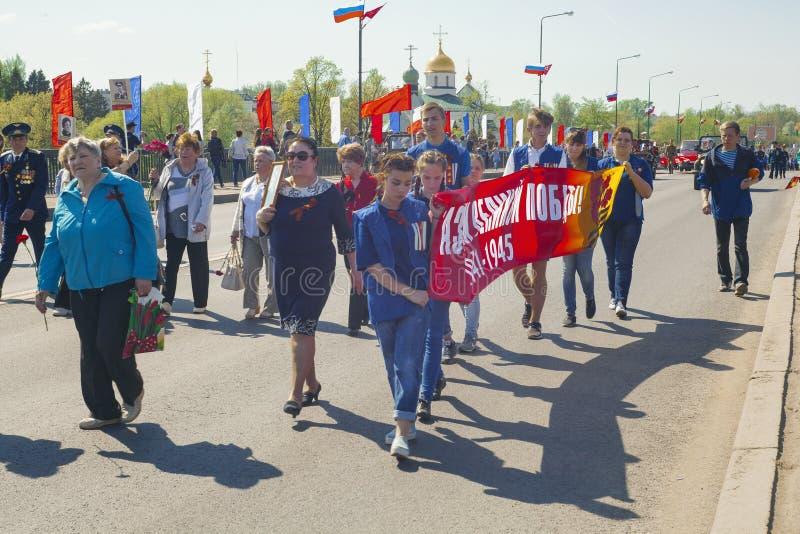ST 彼得斯堡,俄罗斯- 2016年5月9日:集会的青年人举着一副横幅与题字胜利天 免版税库存照片