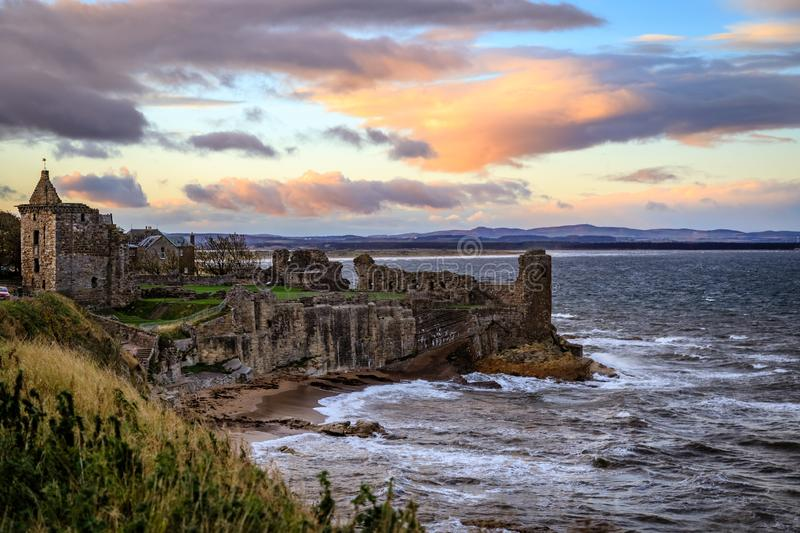 St. Andrews Castle ruins with the high tide and deep orange sunset casting beautiful shadows in Fife, Scotland stock photo