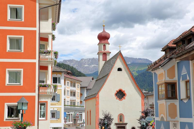 St Antonio Chapel e fachadas coloridas da casa em Ortisei, com as montanhas do grupo de Sella no fundo foto de stock