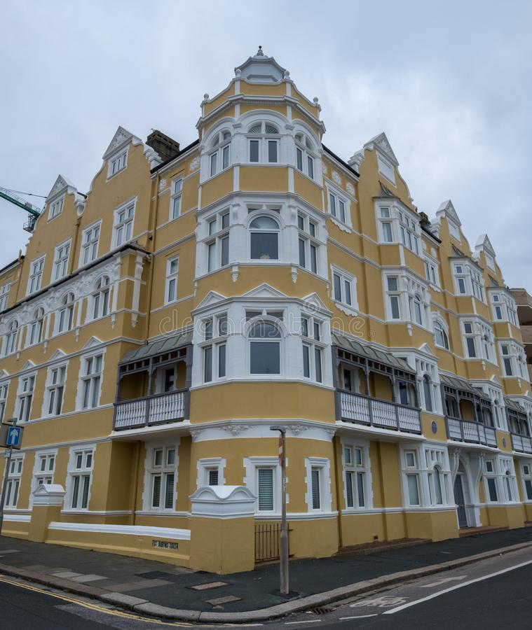 St Aubyns Mansions on Kings Esplanade, Hove, East Sussex, UK. Restored mustard coloured block of flats overlooking the sea royalty free stock photo