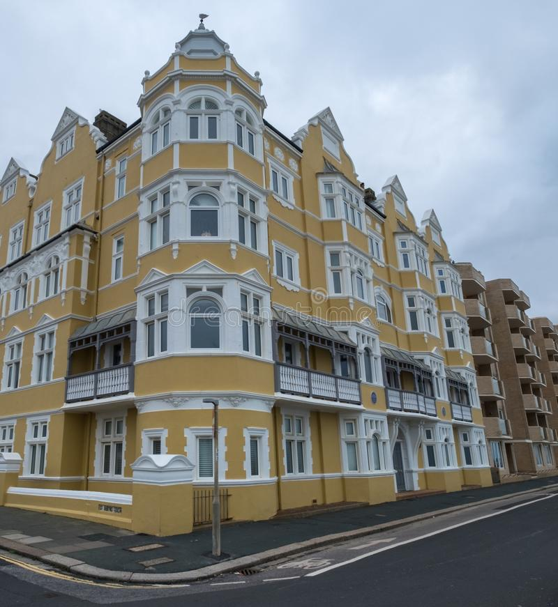 St Aubyns Mansions on Kings Esplanade, Hove, East Sussex, UK. Restored mustard coloured block of flats overlooking the sea stock image