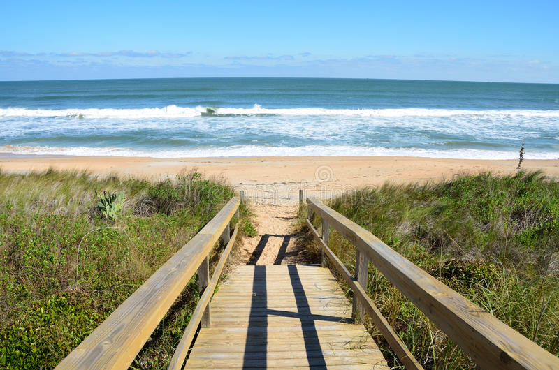 St. Augustine beach. Scenic view of waves breaking on sandy beach with wooden boardwalk over dunes in foreground, St. Augustine, Florida, U.S.A royalty free stock photos