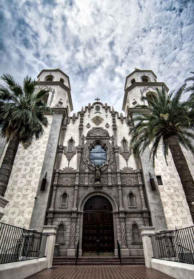 St. Augustine Cathedral in Downtown Tucson, Arizona. Spanish mission style church in southern Arizona framed by Palm trees and a beautiful cloudy royalty free stock images