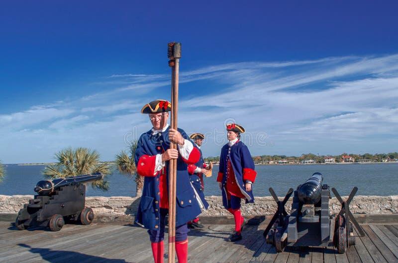 St Augustine, Florida, o estado unido - 3 de novembro de 2018: Os soldados em panos espanhóis tradicionais mostram ao canhão de t imagem de stock royalty free