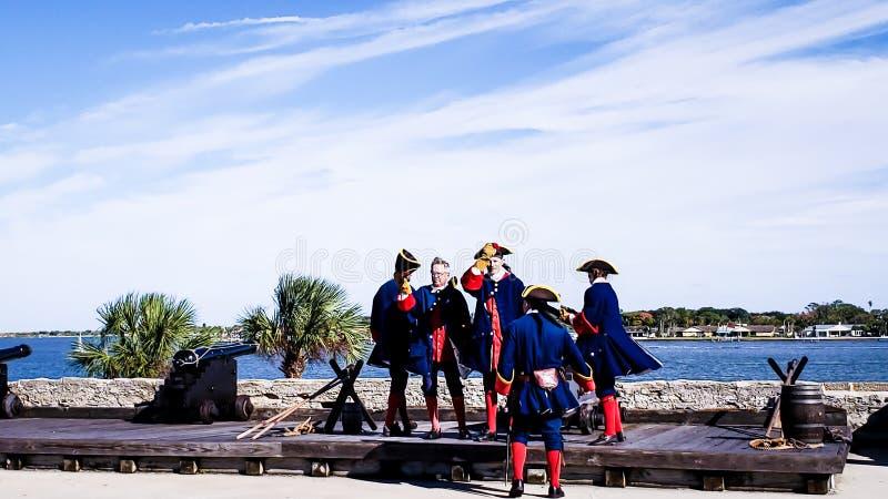 St Augustine, Florida, o estado unido - 3 de novembro de 2018: Os soldados em panos espanhóis tradicionais mostram ao canhão de t fotos de stock