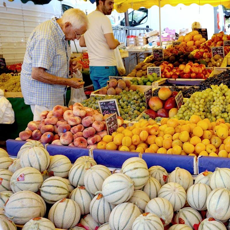 St AYGULF, VAR, PROVENCE, FRANKRIKE, AUGUSTI 26 2016: En kund som kontrollerar kiwin, persikor, druvor, melon och annan frukt på  royaltyfria foton