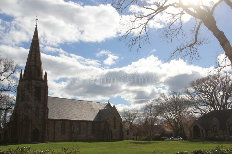 St. Barnabas Memorial Church, Falmouth, Massachusetts, United States. The landmark stone church in the scenic town of Falmouth, with tall steeple and cross on royalty free stock image