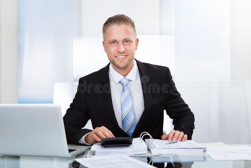St bem sucedido de sorriso do homem de negócios sua mesa imagens de stock