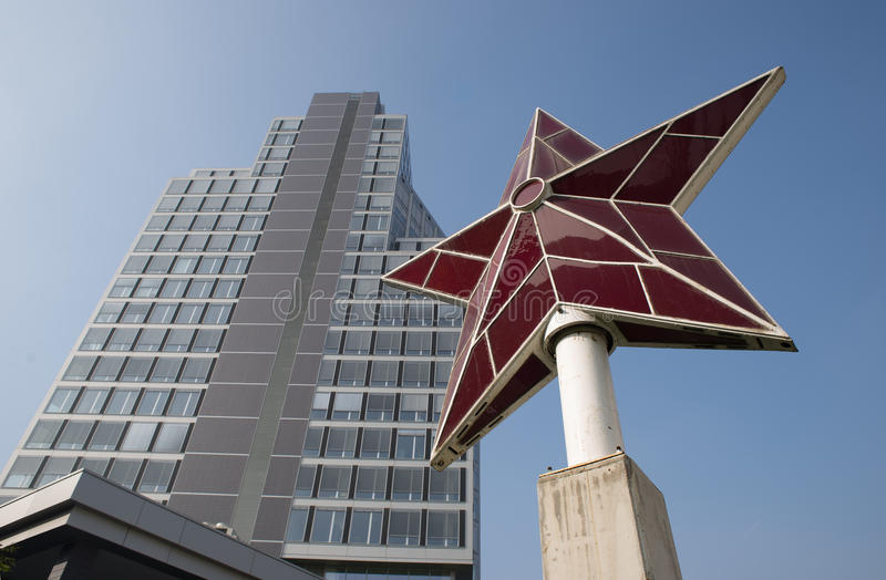 21st century communism. A red star monument is seen in front of a new office building. The red star is the symbol of socialism and communism. These political royalty free stock images
