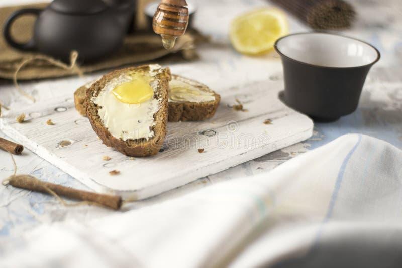 St?cke Brot mit Butter und Honig lizenzfreie stockbilder