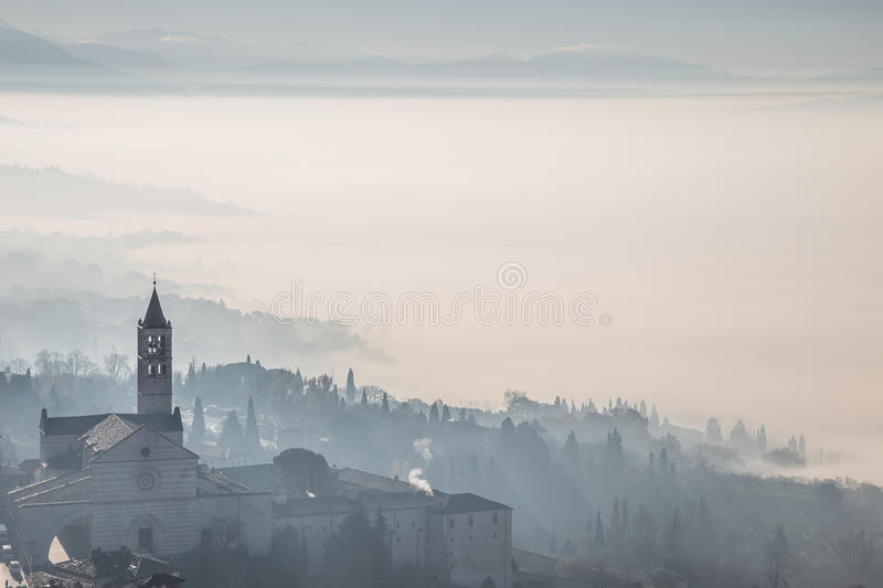 St. Clare church in Assisi with fog. Beautiful view of the St. Clare church in Assisi Italy with fog below and in the background stock images