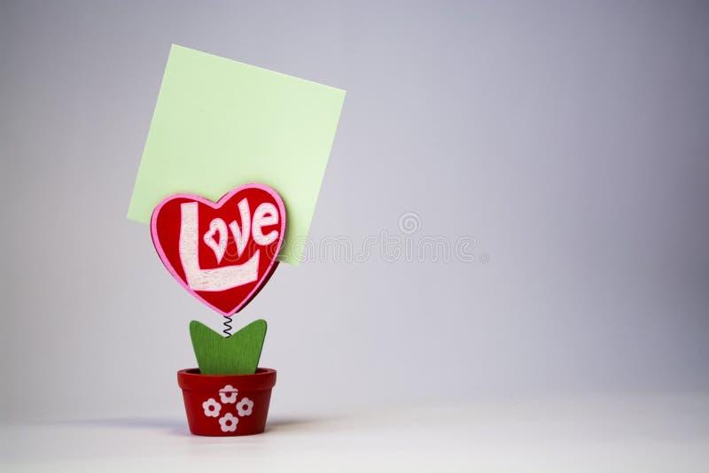 St Dag för valentin` s Röd trähjärta med inskriften 'förälskelse ', På en vår med en klädnypa i en kruka på en vit bakgrund royaltyfria foton