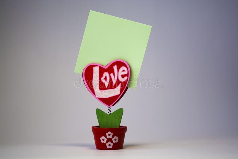 St Dag för valentin` s Röd trähjärta med inskriften 'förälskelse ', På en vår med en klädnypa i en kruka på en vit bakgrund royaltyfria bilder