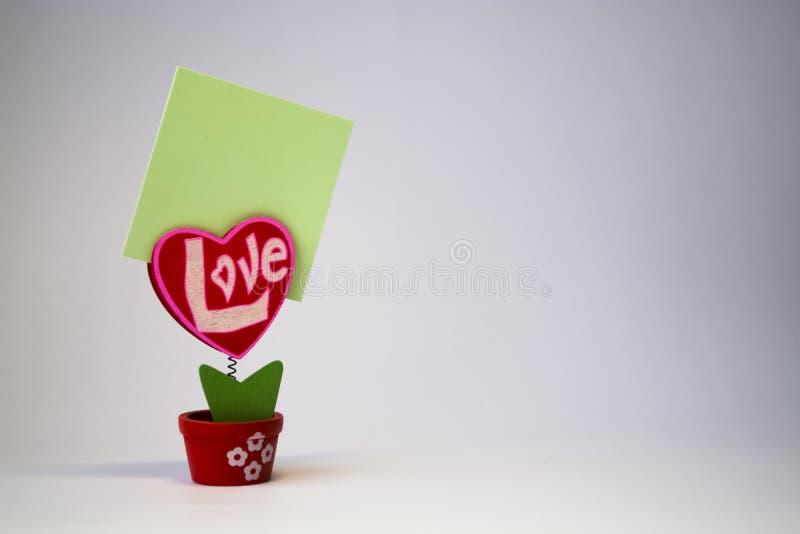 St Dag för valentin` s Röd trähjärta med inskriften 'förälskelse ', På en vår med en klädnypa i en kruka på en vit bakgrund arkivfoto