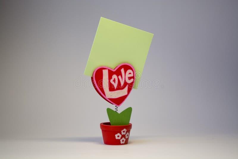 St Dag för valentin` s Röd trähjärta med inskriften 'förälskelse ', På en vår med en klädnypa i en kruka på en vit bakgrund royaltyfri fotografi