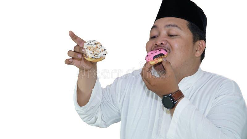 St?ende av asiatiska muslimska m?n, som ?r ?vervikt, tycker om att ?ta tv? donuts med n?je royaltyfri fotografi