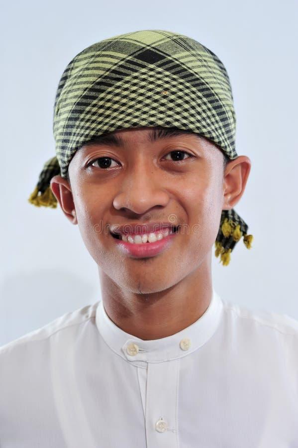 St?ende av att le den asiatiska muslim mannen som v?lkomnar dig arkivbilder