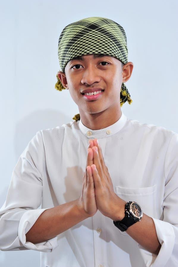 St?ende av att le den asiatiska muslim mannen som v?lkomnar dig arkivbild