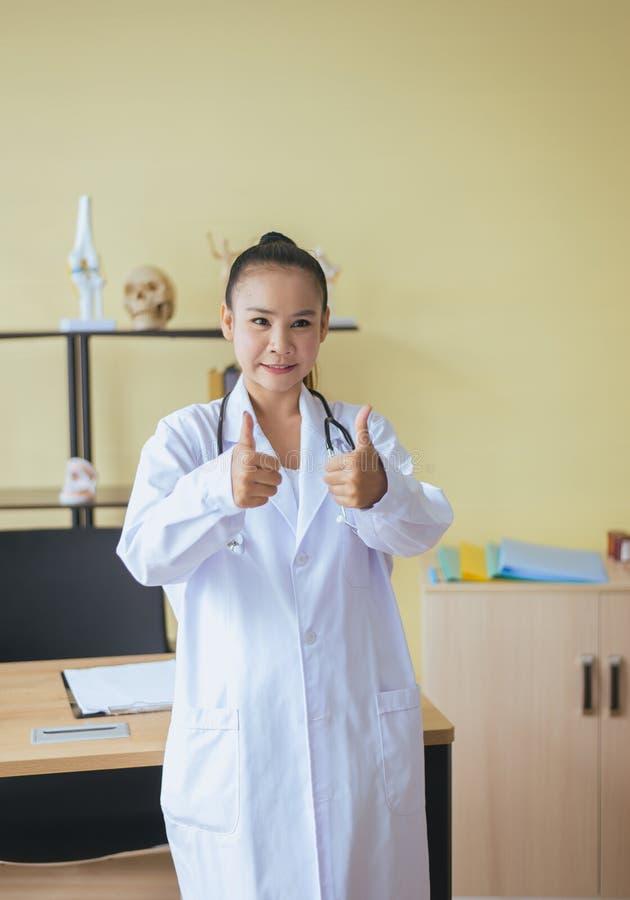 St?ende av att le den h?rliga asiatiska kvinnadoktorn som visar tv? dunsar upp tecken p? lycklig och positiv inst?llningen den sj arkivbilder