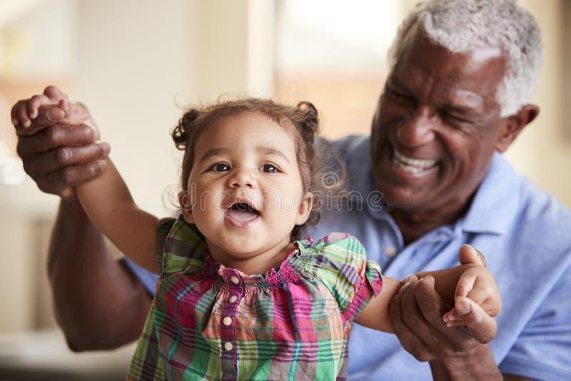 St?ende av att le farfadern som sitter p? den Sofa At Home With Baby sondottern arkivfoto
