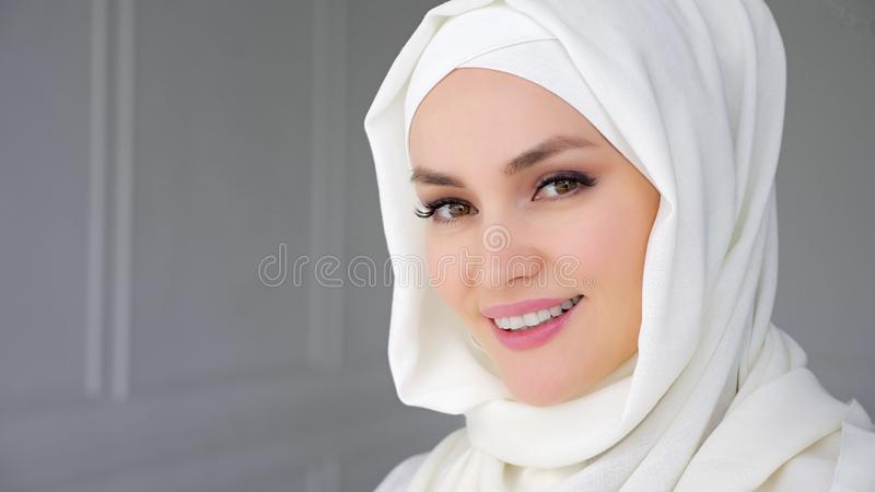St?ende av b?rande hijab f?r muslim arabisk kvinna och att se kameran och att le royaltyfria foton