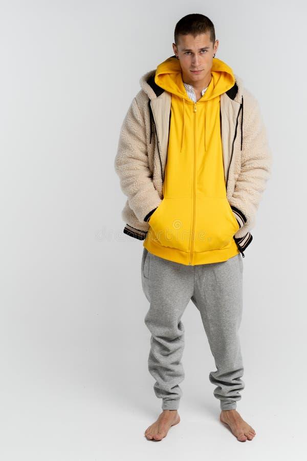 St?ende av den allvarliga attraktiva unga mannen i gul hoodie, att se kameran som isoleras ?ver vit bakgrund royaltyfria foton