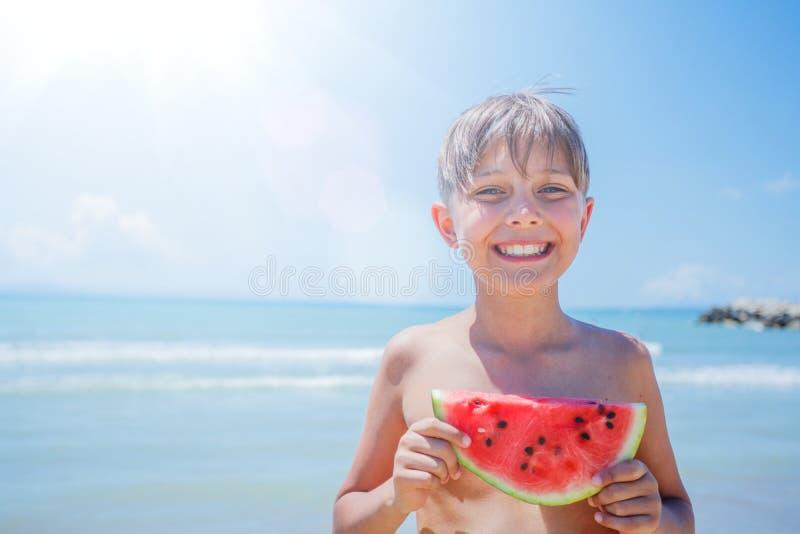 St?ende av den f?rtjusande pojken med vattenmelon p? stranden royaltyfria bilder