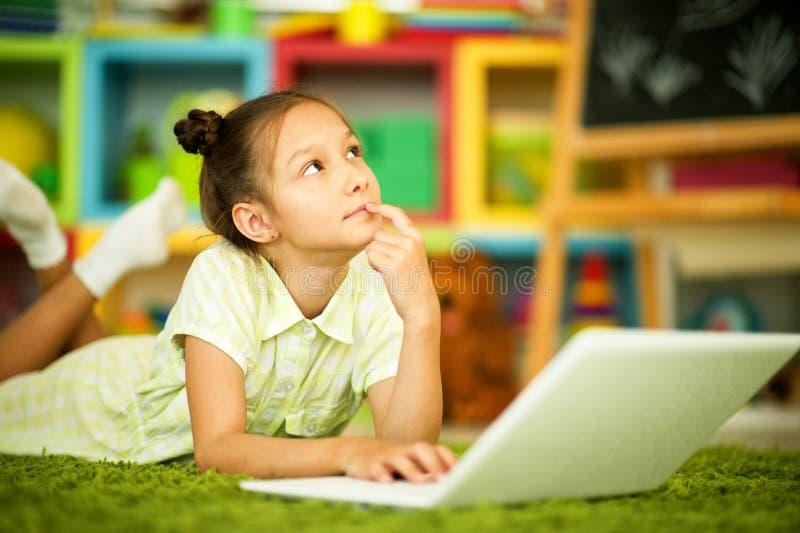 St?ende av den gulliga flickan som hemma anv?nder b?rbara datorn arkivfoton