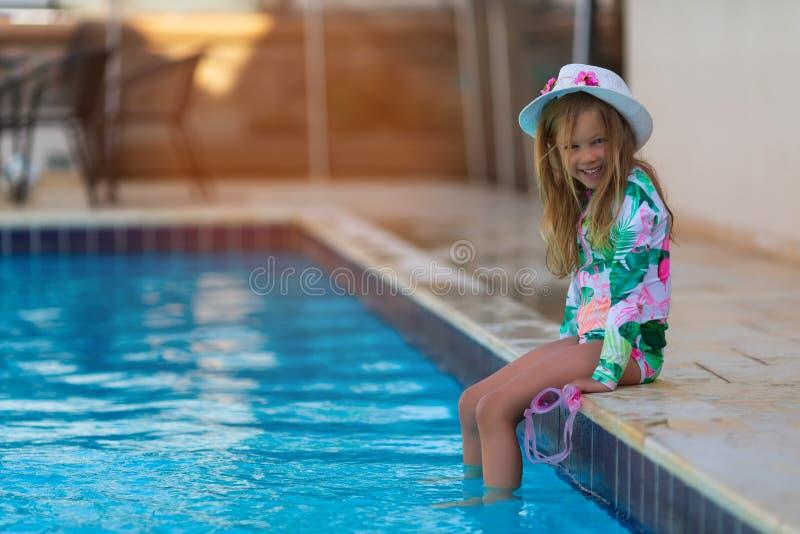 St?ende av den gulliga lyckliga lilla flickan som har gyckel i simbass?ng royaltyfria bilder