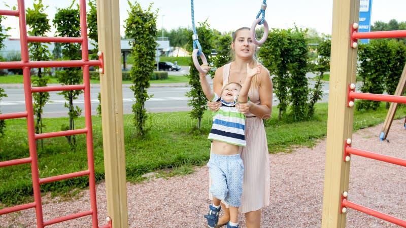 St?ende av den gulliga smilling litet barnpojken som h?nger p? cirklarna med hans moder p? barnlekplats royaltyfri bild
