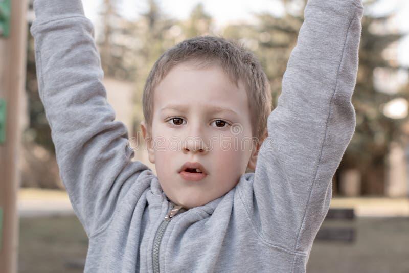 St?ende av den gulliga unga pojken som ser kameran p? barnlekplats F?rtr?ningsbarn som har gyckel p? lekplats Unge som spelar p? arkivbild