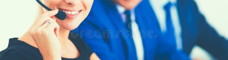 St?ende av den h?rliga aff?rskvinnan i h?rlurar som ler med kollegor i bakgrund arkivfoto