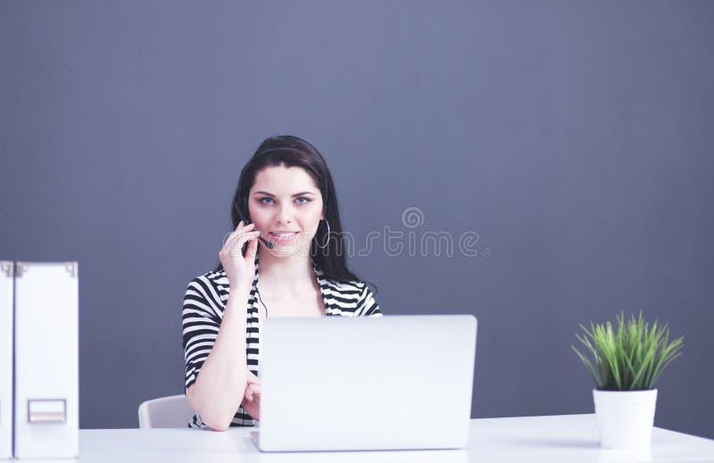 St?ende av den h?rliga aff?rskvinnan som arbetar p? hennes skrivbord med h?rlurar med mikrofon och b?rbara datorn arkivbild