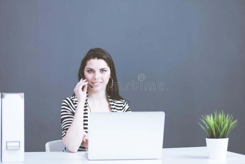 St?ende av den h?rliga aff?rskvinnan som arbetar p? hennes skrivbord med h?rlurar med mikrofon och b?rbara datorn arkivfoto
