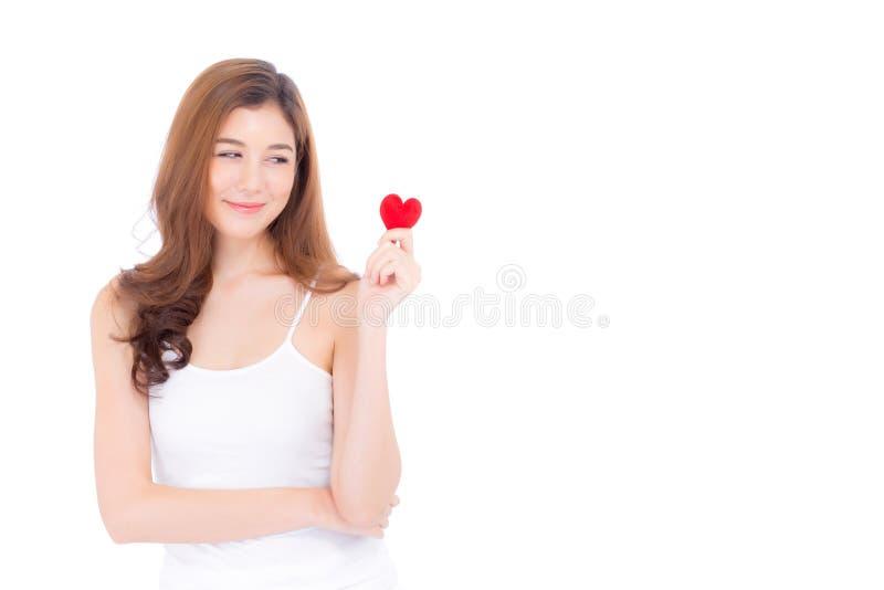 St?ende av den h?rliga asiatiska unga kvinnan som rymmer den r?da hj?rtaformkudden och leende som isoleras p? vit bakgrund royaltyfria foton