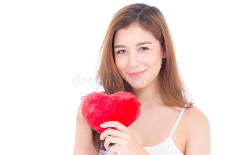 St?ende av den h?rliga asiatiska unga kvinnan som rymmer den r?da hj?rtaformkudden och leende som isoleras p? vit bakgrund, valen fotografering för bildbyråer