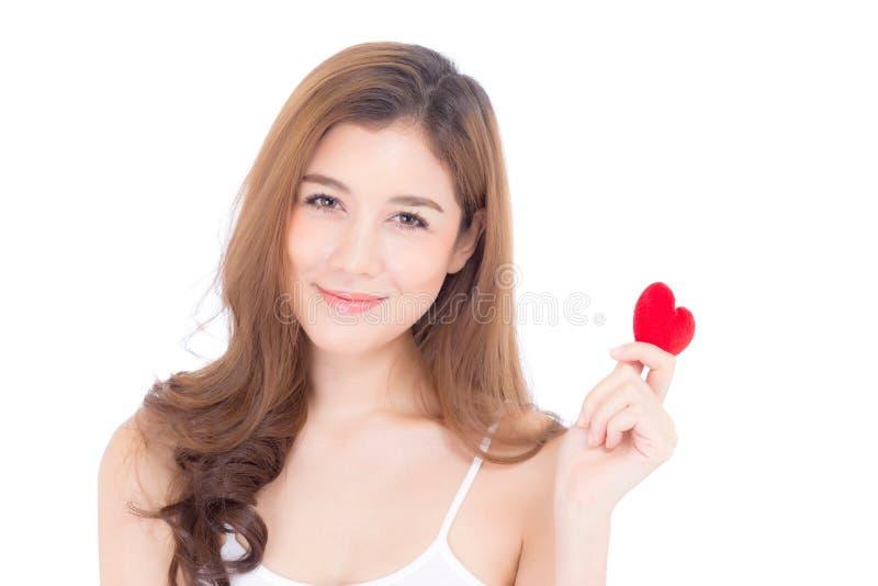 St?ende av den h?rliga asiatiska unga kvinnan som rymmer den r?da hj?rtaformkudden och leende som isoleras p? vit bakgrund arkivfoto