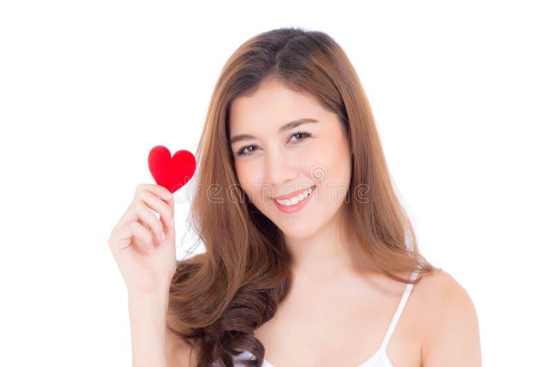 St?ende av den h?rliga asiatiska unga kvinnan som rymmer den r?da hj?rtaformkudden och leende som isoleras p? vit bakgrund royaltyfri foto