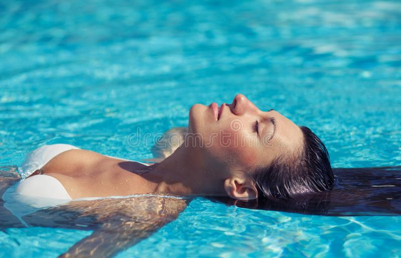 St?ende av den h?rliga brunbr?nda kvinnan i vit swimwear som kopplar av i simbass?ngbrunnsort Varm sommardag och ljust soligt lju arkivfoto