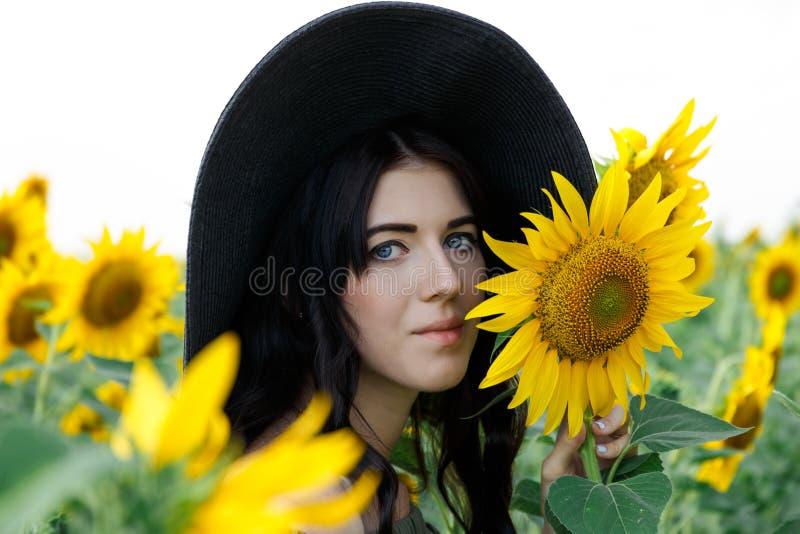St?ende av den h?rliga flickan med solrosor H?rlig s?t flicka i kl?nning och hatt som g?r p? ett f?lt av solrosor royaltyfria bilder