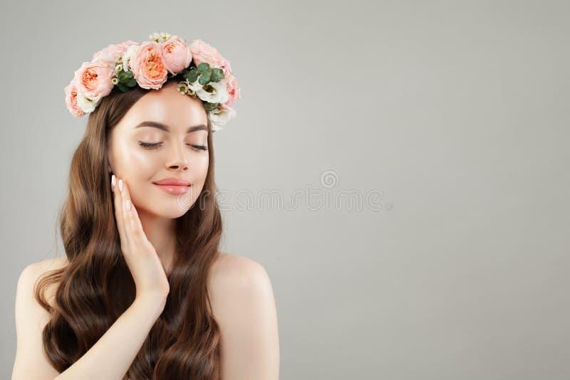 St?ende av den h?rliga le kvinnan med klar hud, l?ngt skinande h?r och blommor Skincare och ansikts- behandlingbegrepp royaltyfri foto