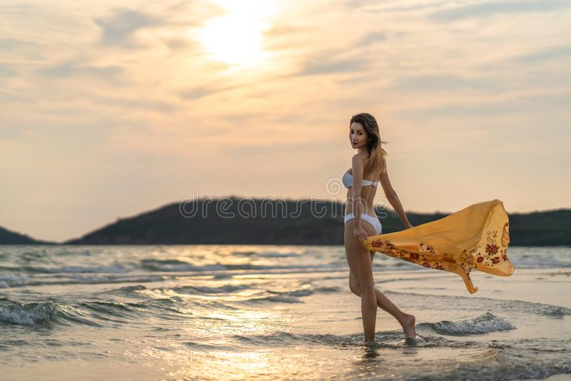 St?ende av den h?rliga sexiga asiatiska flickan i bikini som poserar p? stranden p? solnedg?ngen Modellera fotoforsen, havsloppet royaltyfri fotografi
