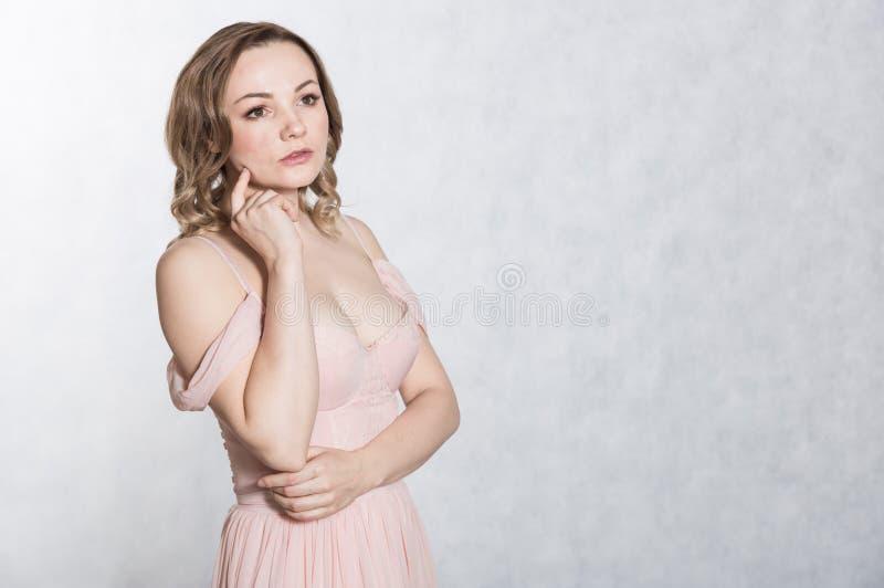 St?ende av den h?rliga unga eleganta kvinnlign i blekt - rosa br?llopskl?nning med den stora urringningen, p? en vit bakgrund royaltyfria bilder