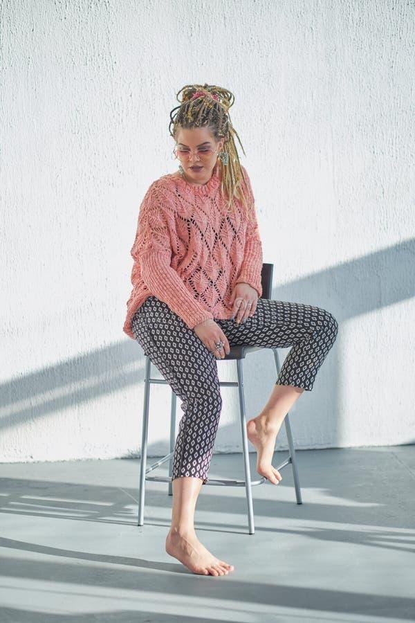 St?ende av den h?rliga unga kvinnan i rosa tr?ja H?rlig kvinna i en tr?ja i nedg?ngen i rosa exponeringsglas i arkivbilder