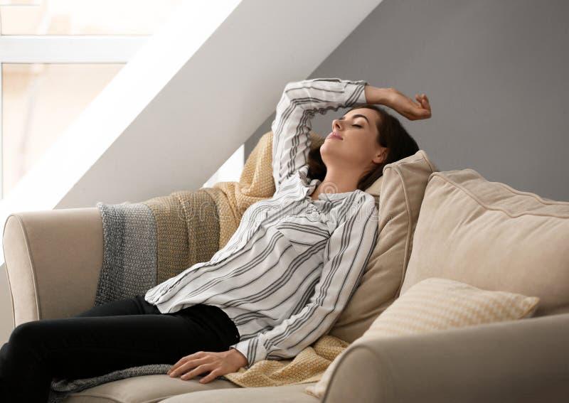 St?ende av den h?rliga unga kvinnan som hemma kopplar av p? soffan arkivbilder