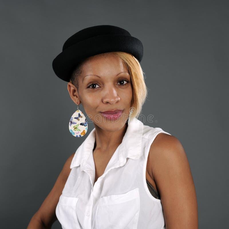 St?ende av den kubanska unga kvinnan i svart hatt royaltyfri bild