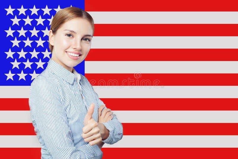 St?ende av den lyckliga amerikanska flickan med tummen upp mot USA flaggabakgrunden Lopp och att l?ra begrepp f?r engelskt spr?k royaltyfri bild