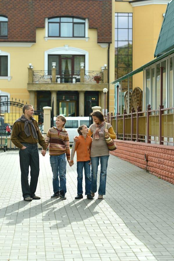 St?ende av den lyckliga familjen av fyra som g?r i staden royaltyfri bild